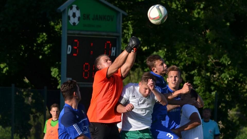 Aleš Pavelec boxuje centrovaný míč od své branky.
