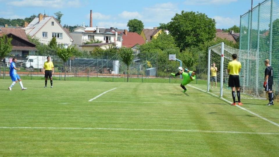 Brankář sezimoústeckého Sokola František Plachý chytá penaltu domácího kapitána Ondřeje Mládka.