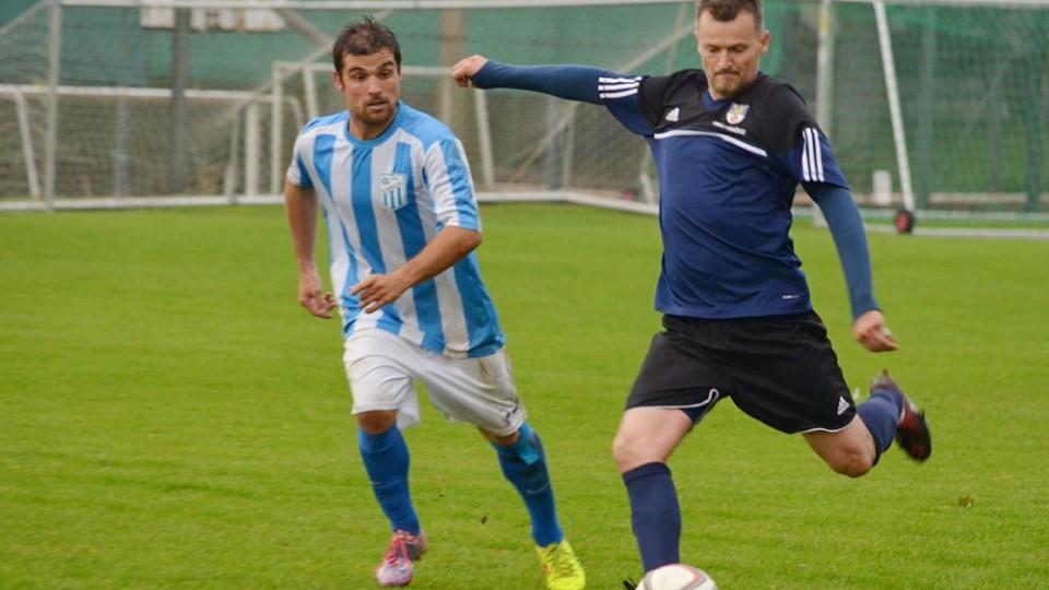 Nestárnoucí zadák Dražic Roman Valášek zahrává míč před Radimem Pouzarem.